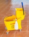 Wischen Sie Eimer und Presse mit Vorsichtzeichen auf dem Boden Lizenzfreie Stockfotografie