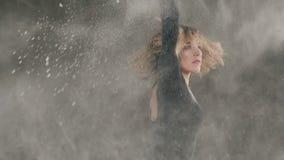 Wischen Sie, weißes Pulver, Mädchen ab, das Tänzer in der schwarzen Kleidung Kreise um an zuhause auf grauem Hintergrund macht fr stock video
