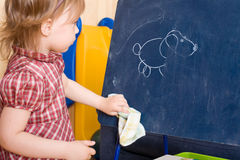 Wischerzeichnung des kleinen Mädchens auf einer Schiefertablette Lizenzfreie Stockbilder