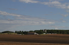 Wisconsin Farm with plowed fields. Farm with plowed field and barns in the distance in summer with a beautiful blue sky with puffy white clouds Stock Photography