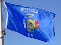 Wisconsin state flag. Wisconsin flag waves in the breeze royalty free stock image