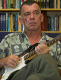 Wisdom Guitar Blues. Famous Croatian guitarist Ante Mazuran practises in front of book ledge Royalty Free Stock Images
