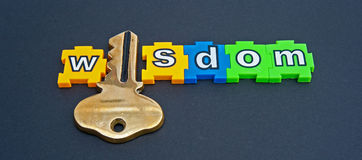 Wisdom is the key. The word wisdom in colorful  jigsaw type lower case letters with the letter 'i' replaced by a golden key isolated on a dark background Royalty Free Stock Photography