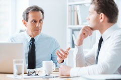 Wise advice for business nice. Two business people in formalwear discussing something while sitting at working place Royalty Free Stock Photos
