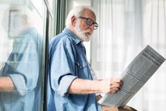 Wise aged man holding journal while based on windowsill. Smart occupation. Side view of interested pensioner reading favorite column in fresh newspaper stock photo