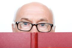 Wise grandfather in glasses holding book Stock Images