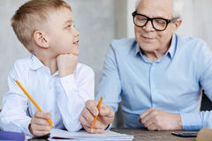 Wise helping man proofreading grandsons essay. Personal tutor. Clever interested original kid sitting at the table and waiting while grandpa helping him and Stock Image