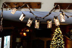 Wise men Christmas decoration. Antiqued paper on a string with the words wise men and a glowing Christmas tree in the background Royalty Free Stock Photos