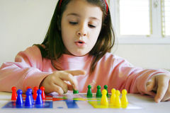 A wise move. Little six year old girl alone at home, carefully arranging her pawns on the table for a game Stock Image