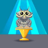 Wise owl with a book on the blue background. Statuette on a gold Royalty Free Stock Photos