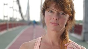 Wise and peaceful senior woman looking at camera. Closeup portrait of beautiful senior redhead sporty woman looking at camera and playing with hair after running stock video footage