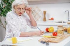 Wise senior woman working with utility bills Stock Photos