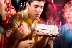 Wish. Man with his friends blow out candle on cake at birthday Stock Photo
