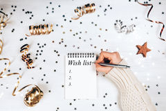 Wish lift for New Year. Holiday decorations and notebook with wish list on white rustic table, flat lay style. Planning concept Royalty Free Stock Photos