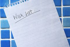 Wish List. Note paper showing a blank 'Wish list' stuck to blue tiled background Royalty Free Stock Photo