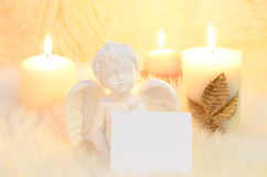 Wish list. An angel surrounded by candles holding a empty sheet for wish list royalty free stock photography