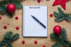 Wish list for Christmas in German on a notepad with Christmas de Stock Image