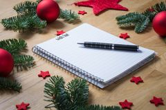 Wish list for Christmas on a notepad with Christmas decorations. And fir branches on a wooden table seen from the side Royalty Free Stock Photo