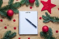 Wish list for Christmas on a notepad with Christmas decorations. And fir branches on a wooden table from above Stock Photos