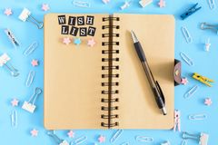 Wish list. Notepad with brown sheets and an inscription . Confusion of office supplies. Clips, clothespins and small. Wish list. Notepad with brown sheets and an Stock Images