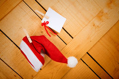 Wish list and Santa cap. Wish list and Santa  cap hanging on a rustic wooden door Royalty Free Stock Photos
