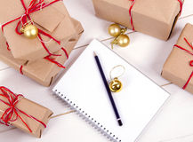 Wish list in to notebook near christmas gifts Royalty Free Stock Photo