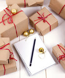 Wish list in to notebook near christmas gifts Royalty Free Stock Photography