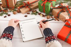 Wish list for xmas. Women hands with notebook and pen. Fir branch, bells, cinnamon, nuts. New year concept. Women hands with notebook and pen. Creative presents Stock Photos