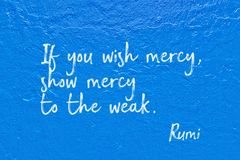 Wish mercy Rumi. If you wish mercy, show mercy to the weak - ancient Persian poet and philosopher Rumi quote handwritten on blue wall Stock Images