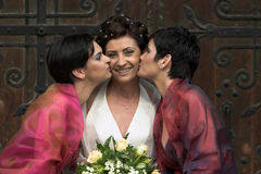 We wish you good luck. Two younger women give a kiss to an older one  - they are mother and daughters. This is a wedding shot and the mother is the bride Royalty Free Stock Images