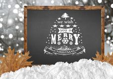We Wish You A Merry Christmas on blackboard with blurr forest and leaves Stock Photo