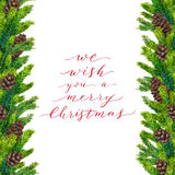 We wish you a Merry Christmas text on watercolor border. Of fir branches and fir-cones, xmas lettering on watercolour hand painted frame for holiday card Royalty Free Stock Image