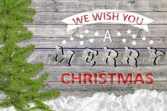 We Wish You A Merry Christmas on wooden board with pine and snow Royalty Free Stock Photography