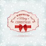 We wish you a very Merry Christmas background. We wish you a very Merry Christmas ornate banner with red ribbon and a bow, on winter background with snow and Royalty Free Stock Photography