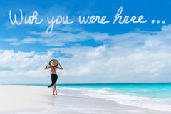 Wish you were here cloud message on beach vacation. Wish you were here cloud message written in sky above woman walking on beach vacation Luxury travel Caribbean Stock Photography