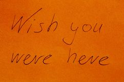 Wish you were here on paper. `Wish you were here` handwritten on orange paper royalty free stock photography