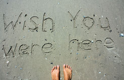 Wish you were here writing. A message written in the sand that says wish you were here stock photos