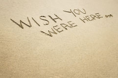 Wish you were here written in the sand. Stock Photography
