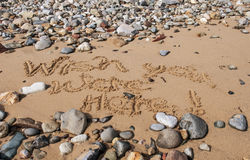 Wish You Were Here. Written in wet sand on pebble beach Royalty Free Stock Photo