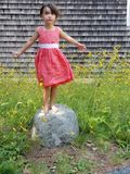 Wishes she could fly. A little girl stands upon a rock, arms outstretched like a bird about to take flight.  Her expression as she looks towards the sky and Royalty Free Stock Photos