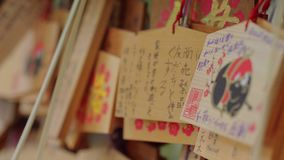 Wishes written on wooden plates in a Buddhist Temple in Japan - TOKYO / JAPAN - JUNE 12, 2018. Wishes written on wooden plates in a Buddhist Temple in Japan stock video footage