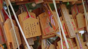 Wishes written on wooden plates in a Buddhist Temple in Japan - TOKYO / JAPAN - JUNE 12, 2018. Wishes written on wooden plates in a Buddhist Temple in Japan stock footage