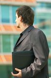 Wishful Businessman. Young professional man holding a briefcase under his arm, looking toward an office building Stock Photos