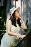 A Wishful Lady. A mulling Asian lady by a wooden house Stock Photo