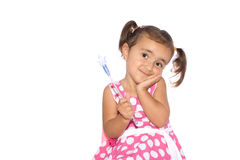 Wishful Thinking Little Girl With A Wand. A little girl wearing a dress with polka dots, holding a magic wand with a blue semitransparent star, using the hair Royalty Free Stock Photos