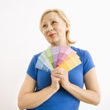 Wishful woman with paint swatches. Portrait of smiling adult blonde woman holding paint swatches with hopeful expression Royalty Free Stock Image