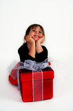 Wishing. A little girl sits with her package and daydreams royalty free stock image