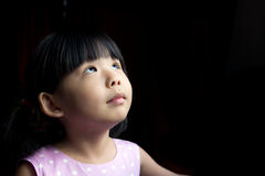 Wishing. Little child is making a wish isolated in dark background Royalty Free Stock Photography