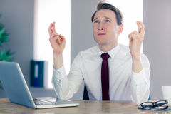 Wishing businessman crossing his fingers. In his office Royalty Free Stock Photography