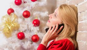 Wishing everyone merry christmas. Christmas wishes concept. Woman pretty peaceful dreamy face hold smartphone enjoy. Mobile phone conversation. Girl sit near stock photos